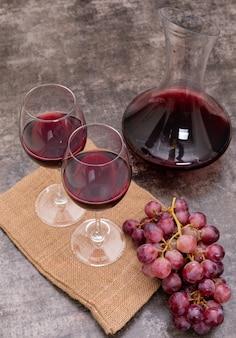 Vista lateral vinho tinto no jarro e copos de saco na pedra escura vertical