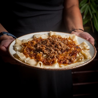 Vista lateral xengel com cebola picada e frita e mão humana em prato redondo