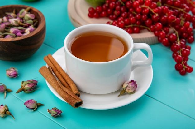 Vista lateral xícara de chá com canela e groselha com botões de rosa secos, sobre um fundo azul claro