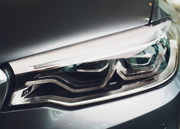 Vista macro do farol azul moderno da lâmpada de xénon do carro.