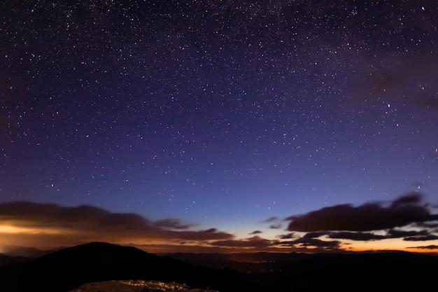 Vista mágica da base de esqui à noite com vista para a aurora boreal em uma noite nublada de inverno