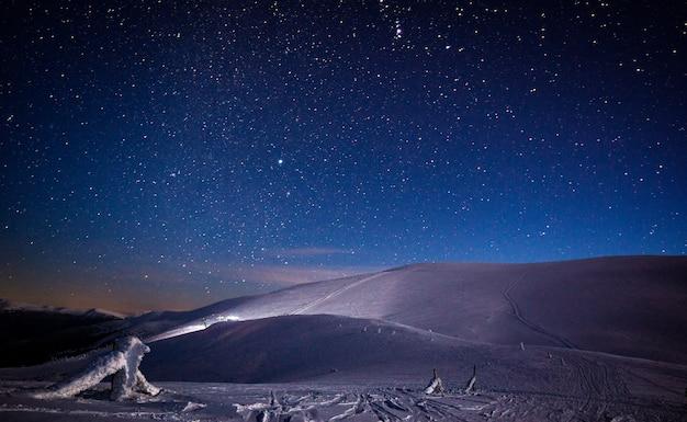 Vista mágica das colinas e montanhas cobertas de neve e pistas de esqui contra o céu estrelado fascinante. o conceito de natureza de inverno e recreação ao ar livre