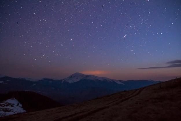Vista majestosa do céu estrelado fantástico sobre as magníficas montanhas dos cárpatos, cobertas por uma floresta sempre verde e picos nevados à distância. panorama deslumbrante da beleza e magia da natureza.