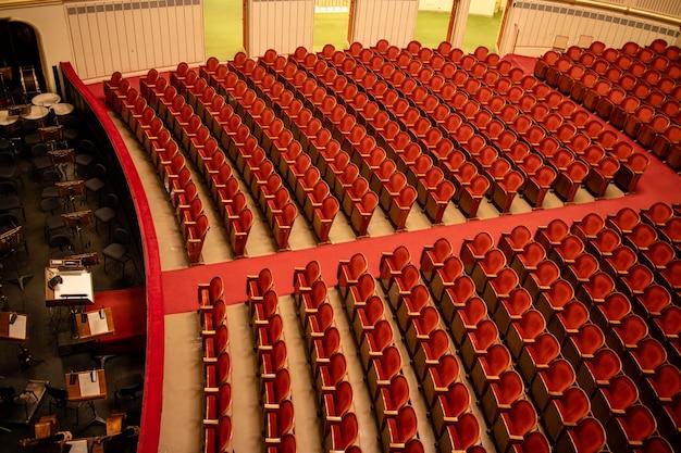 Vista maravilhosa da sala de concertos do teatro do auditório da ópera estatal de viena em viena, áustria - parterre vazio com assentos vermelhos nas filas, sem pessoas e parte do fosso da orquestra.