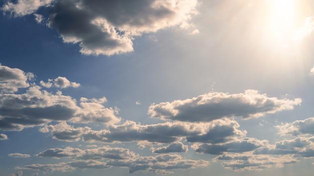 Vista maravilhosa do céu de nuvens cumulus com a luz do sol do verão. cloudscape bonito como panorama de fundo da natureza. tempo de luz natural do sol amarelo