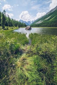Vista meditativa para o lindo lago com pedra no vale nas montanhas nevadas