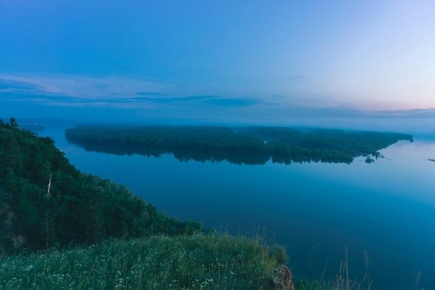 Vista mística da costa no rio largo com água lisa. margem do rio da grande ilha com floresta sob a névoa. neblina precoce acima das árvores.