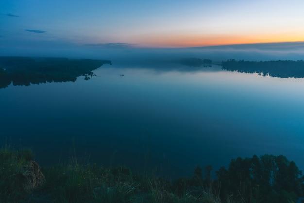 Vista mística da costa no rio largo. margem do rio com a floresta sob a névoa. neblina precoce acima das árvores. brilho laranja no céu pitoresco antes do amanhecer.