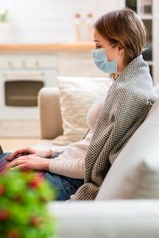 Vista moderna da mulher com máscara sentado no sofá
