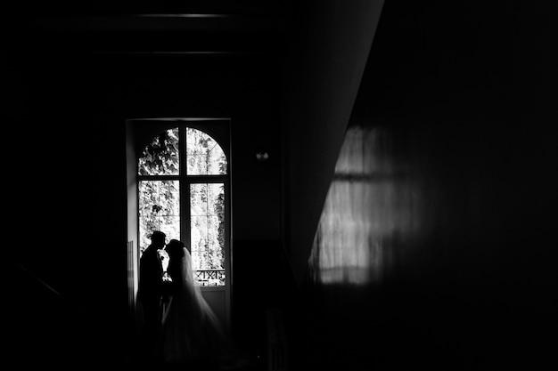 Vista monocromática da silhueta do casal de noivos que está quase se beijando perto da janela