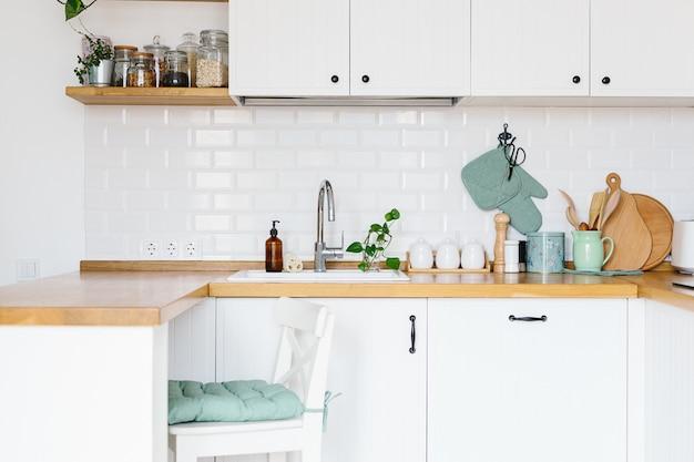 Vista na cozinha branca em estilo escandinavo, detalhes de cozinha, plantas na mesa de madeira