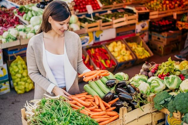 Vista na jovem mulher comprando legumes no mercado.