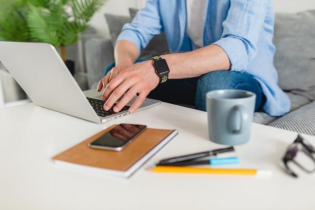 Vista na mesa no local de trabalho close-up das mãos do homem em casa trabalhando digitando no laptop