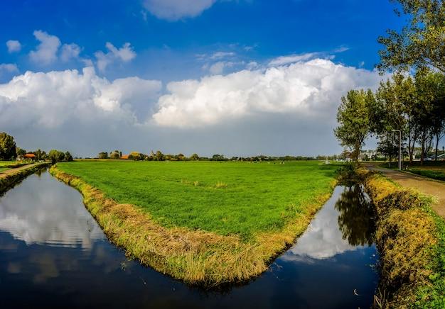 Vista na pequena vila 't woudt em uma paisagem típica de polder holandês.