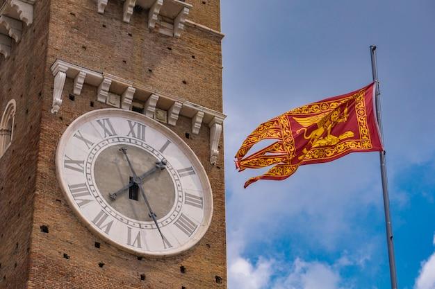 Vista na torre dei lamberti e a bandeira da república de veneza em verona, itália