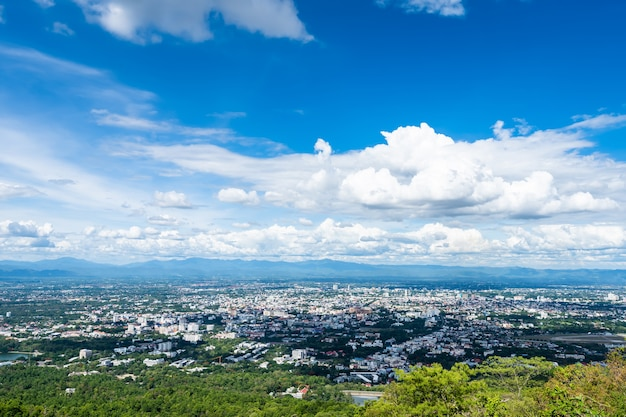 Vista nas montanhas com a paisagem urbana sobre a textura clara abstrata do fundo do céu azul brilhante da cidade airatmosphere com nuvens brancas. de chiang mai, tailândia