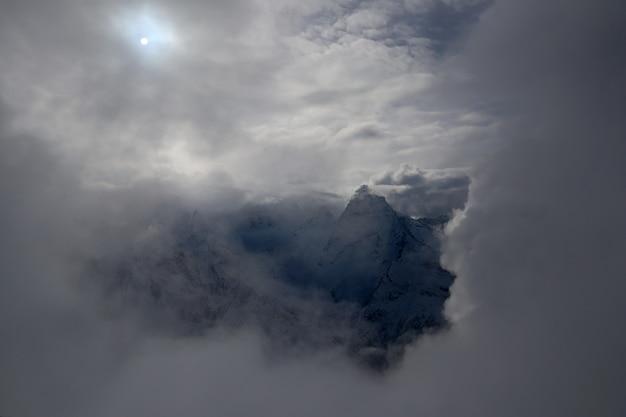 Vista nas montanhas nevadas do pico do cáucaso por entre as nuvens