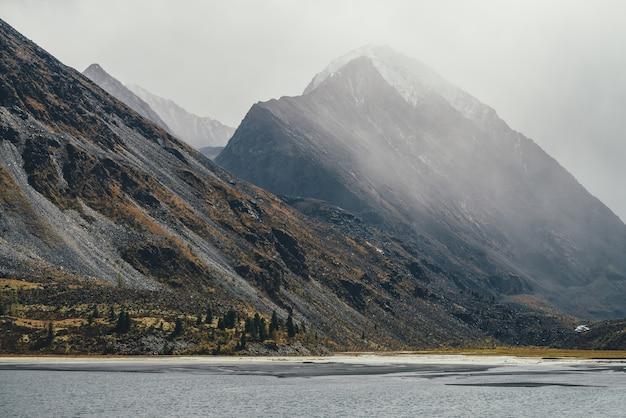Vista nebulosa do outono sombrio para o lago da montanha cinza e o pináculo rochoso com neve no topo em neblina em tempo chuvoso. paisagem atmosférica montanhosa enevoada com rochas nas cores do outono, sob um céu nublado cinza.