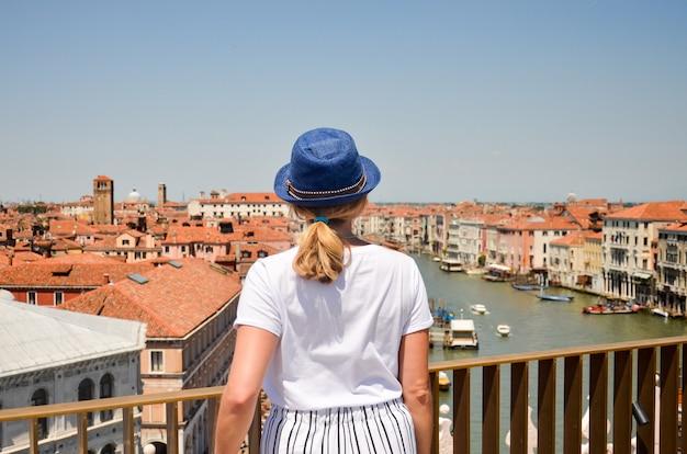 Vista no grand canal com viajante de mulher com chapéu de palha. vista traseira com espaço de cópia. jovem viajante do sexo feminino
