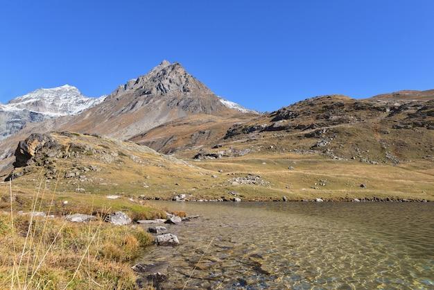 Vista no lago no parque nacional de vanoise, na frança, com fundo de montanhas nevadas sob o céu azul