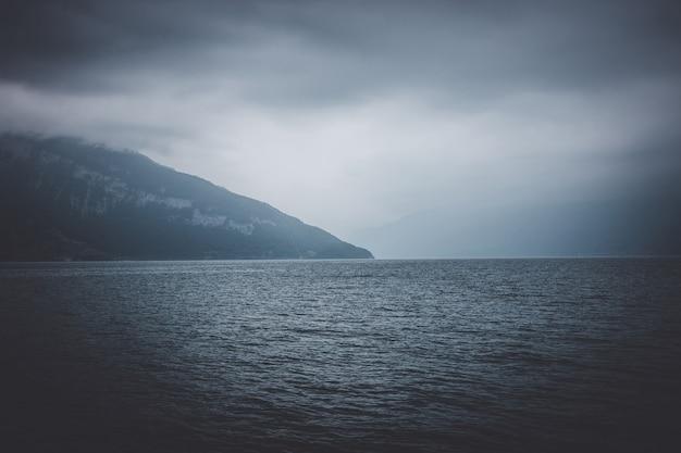 Vista no lago thun e montanhas do navio na cidade de spiez, suíça, europa. cena dramática de nuvens azuis temperamentais