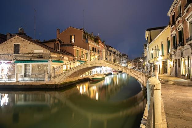 Vista noturna da arquitetura antiga iluminada, barcos flutuantes e reflexos de luz na água dos canais