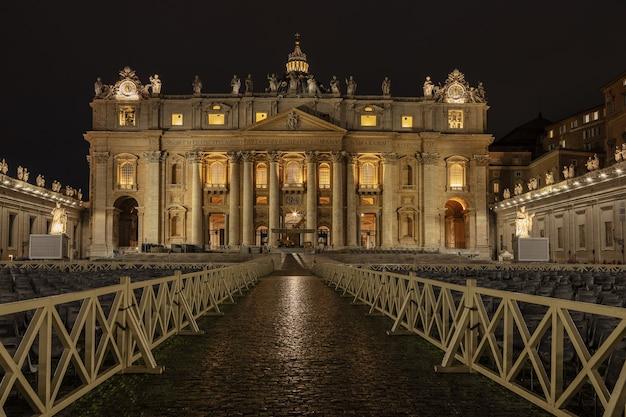 Vista noturna da iluminada basílica de são pedro vaticano roma