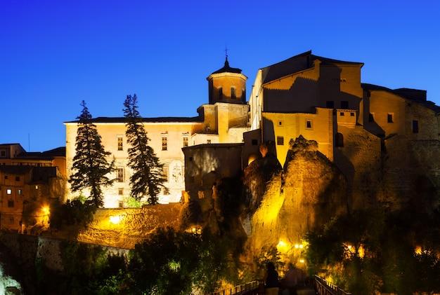 Vista noturna de casas medievais sobre rochas