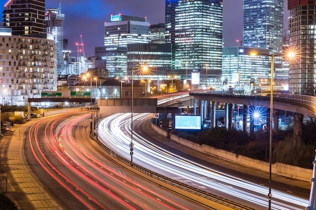Vista noturna de cidade com arranha-céus e trilhas de semáforo