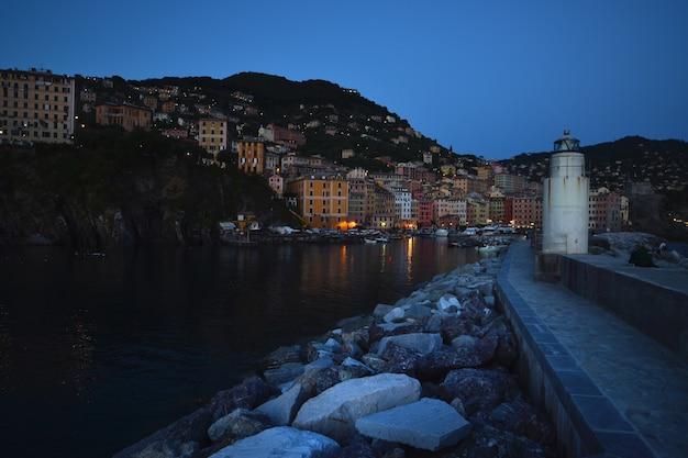 Vista noturna do pequeno porto e do farol de camogli