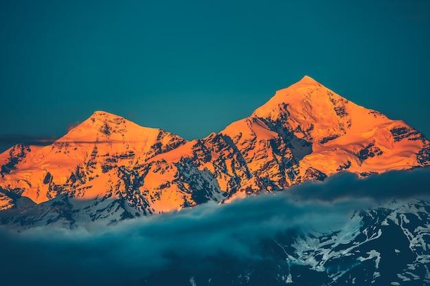 Vista noturna do pôr do sol no pico nevado da montanha com nuvens enevoadas