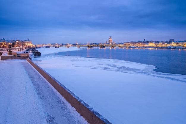 Vista noturna do rio neva e da ponte no inverno, são petersburgo, rússia