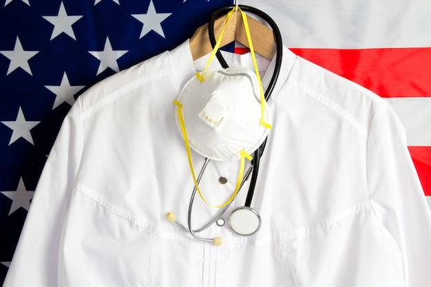 Vista os médicos com um estetoscópio e uma máscara médica em um fundo com bandeira dos eua