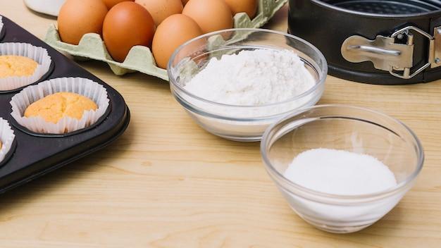Vista panoramic, de, açúcar, e, farinha, tigela, com, ovos, e, cupcakes, ligado, tabela madeira