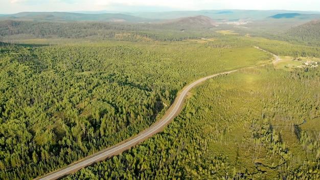 Vista panorâmica aérea do drone de aldeia rural entre campos, florestas, rios e colinas. estrada e rodovia vazias, vista panorâmica.