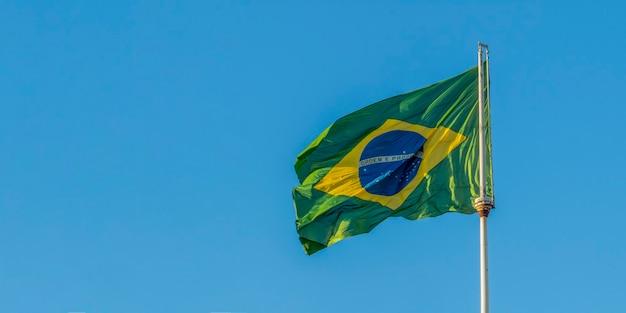 Vista panorâmica com bandeira brasileira. bandeira do brasil tremulando ao vento. ordem e progresso.