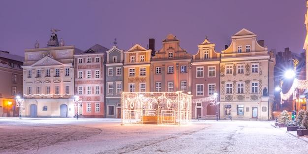 Vista panorâmica com casas de comerciantes e fonte decorada na praça do mercado velho na cidade velha na noite de natal, poznan