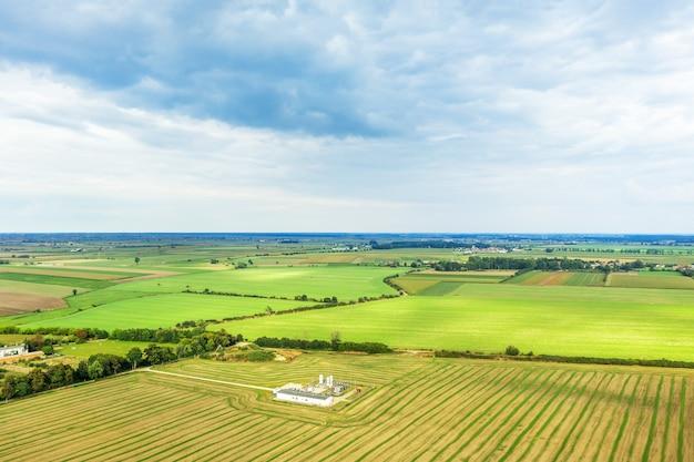 Vista panorâmica costurada de uma grande altura em campos coloridos, contra o fundo do céu azul de verão, paisagem de verão com um drone, fieldama verde
