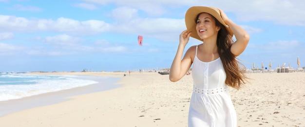 Vista panorâmica da bandeira de uma jovem feliz, segurando seu chapéu de palha andando na praia deserta em um dia ventoso