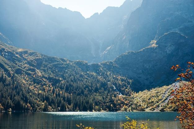 Vista panorâmica da bela natureza verde, montanhas rochosas e o lago morskie oko com as luzes do sol matinal ao redor