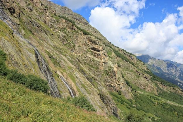 Vista panorâmica da cena de montanhas no parque nacional de dombay, cáucaso, na rússia. paisagem de verão, clima ensolarado, céu azul dramático e dia ensolarado