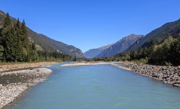 Vista panorâmica da cena do rio nas montanhas do parque nacional de dombay, cáucaso, rússia, europa. céu azul dramático e paisagem ensolarada de verão