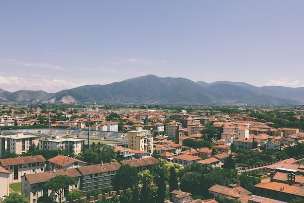 Vista panorâmica da cidade de pisa com edifícios históricos e montanhas distantes da torre de pisa. dia de verão e céu azul ensolarado