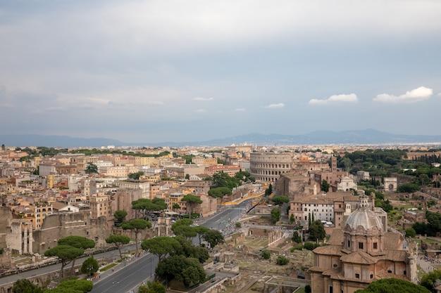 Vista panorâmica da cidade de roma com o fórum romano e o coliseu do monumento vittorio emanuele ii, também conhecido como vittoriano. dia ensolarado de verão e céu azul dramático