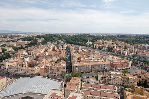 Vista panorâmica da cidade de roma da basílica papal de são pedro (basílica de são pedro). dia de verão, pessoas andam na rua e carros na estrada