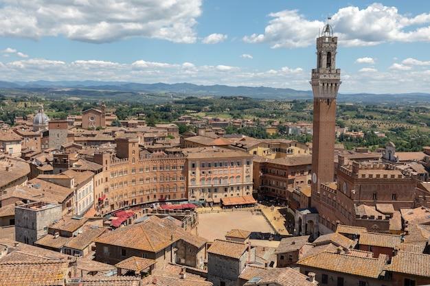 Vista panorâmica da cidade de siena com a piazza del campo e a torre del mangia é uma torre na cidade da catedral de siena (duomo di siena). dia ensolarado de verão e céu azul dramático