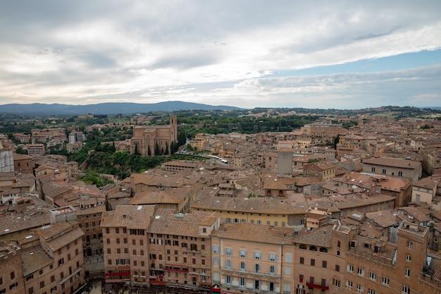 Vista panorâmica da cidade de siena com edifícios históricos e campos verdes distantes da torre del mangia é uma torre na cidade. dia ensolarado de verão e céu azul dramático