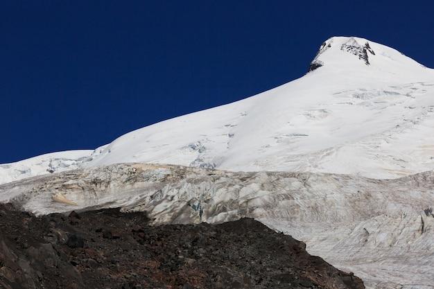 Vista panorâmica da encosta sul do monte elbrus e da pequena geleira azau das montanhas do cáucaso, na rússia. dois picos de montanha coberta de neve.