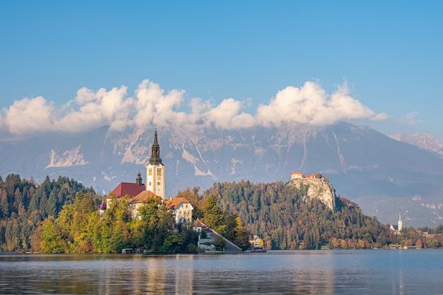 Vista panorâmica da ilha no lago bled com a igreja de peregrinação da assunção de maria, com reflexão. eslovênia, europa.