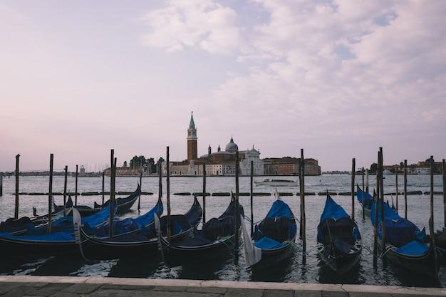 Vista panorâmica da laguna veneta da cidade de veneza com gôndolas e a ilha de san giorgio maggiore. paisagem de manhã de verão e céu azul dramático